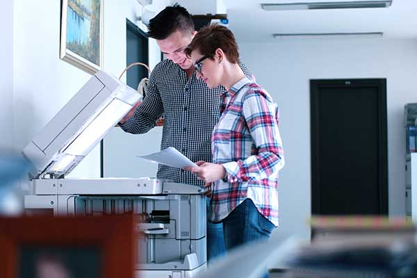 Two coworkers scanning a printed page