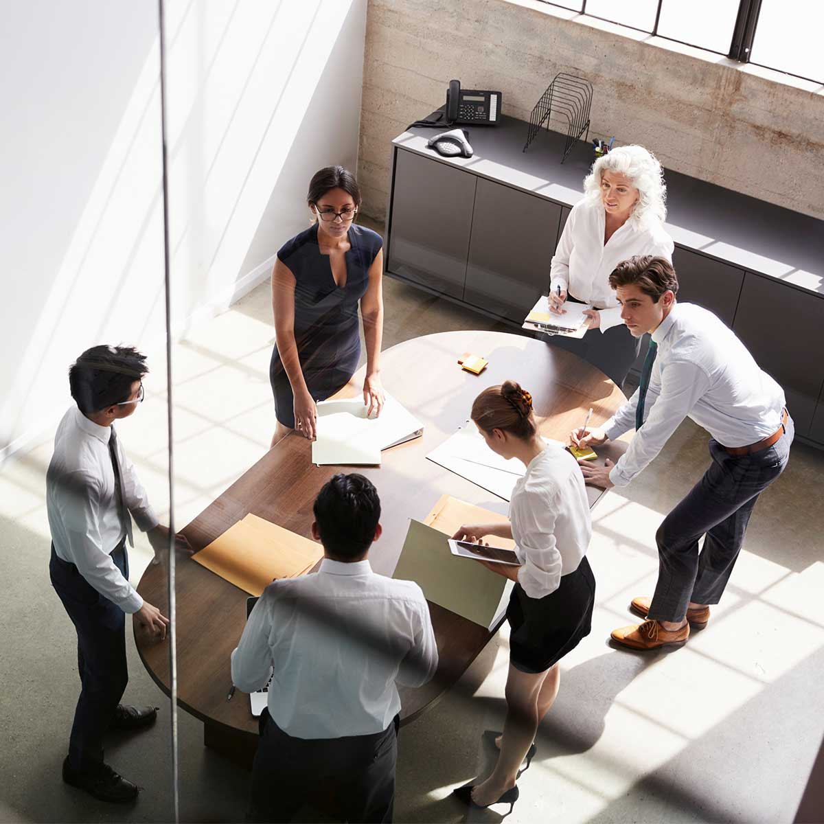 Employees gathered around a conference table discussing print documents